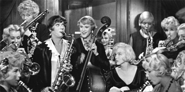 Tony Curtis e Jack Lemmon travestiti da donna, mentre suonano insieme a Marilyn Monroe. ©AshtonProductions/MirischCompany